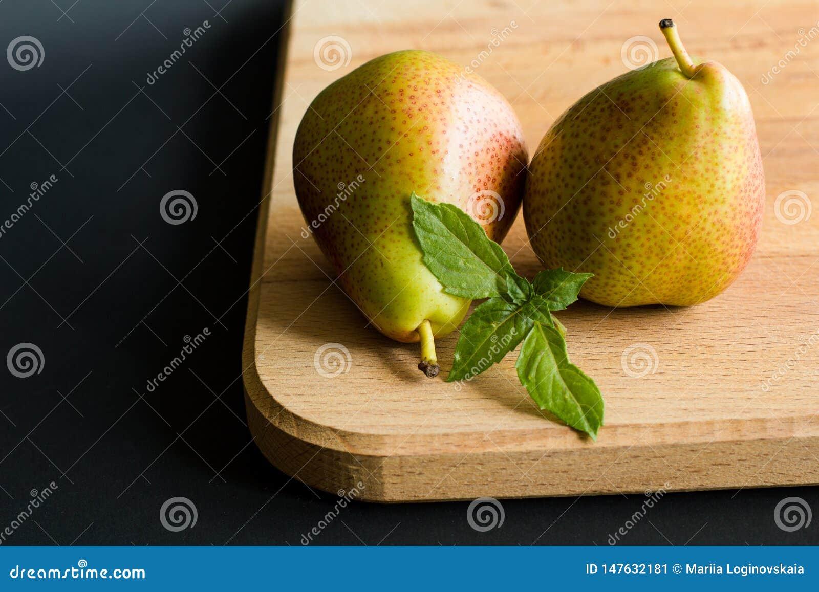 Duas peras com as folhas frescas da manjericão em uma placa de corte de madeira com fundo preto