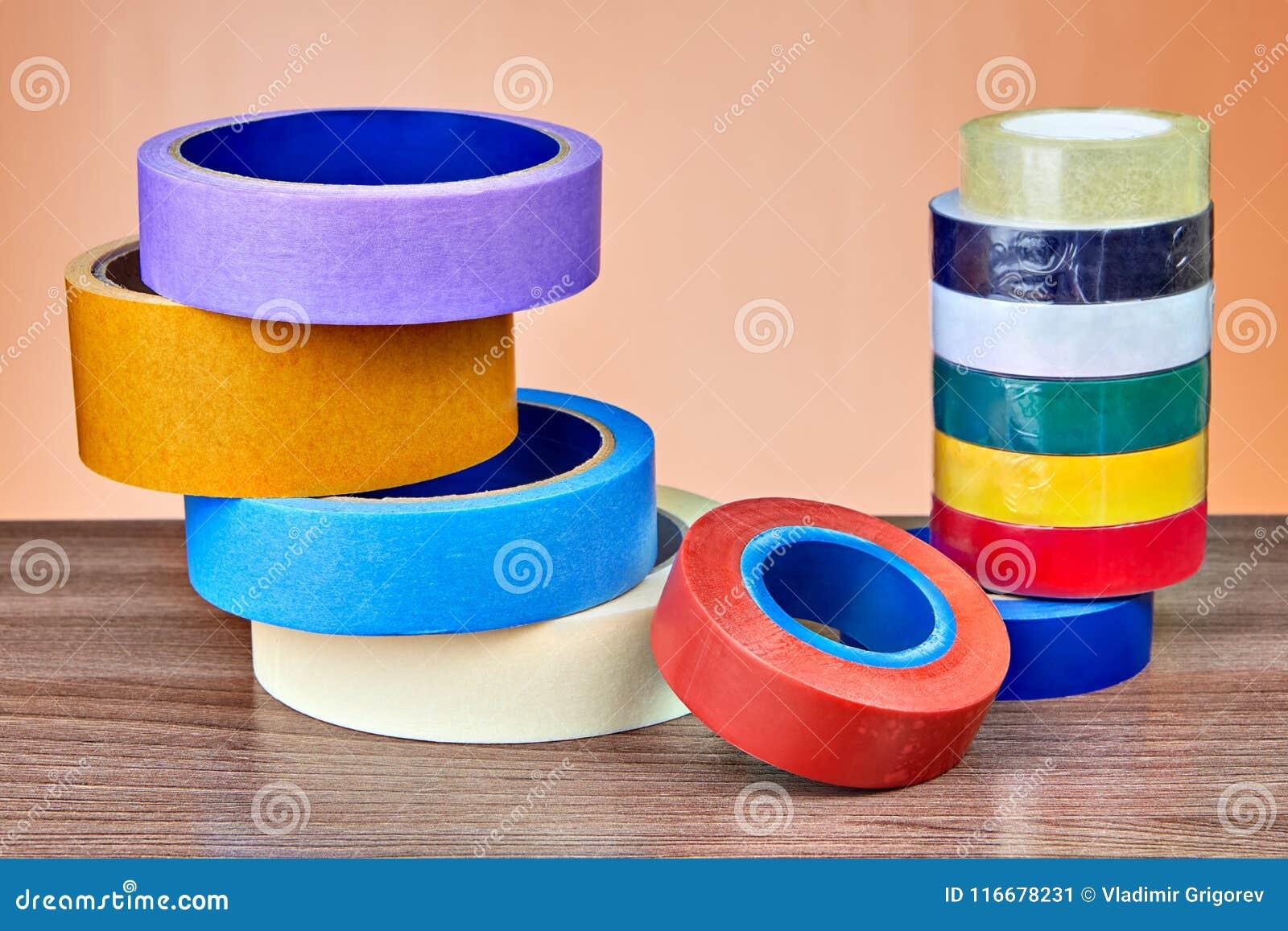 Duas pilhas de rolos da fita adesiva multi-colorida