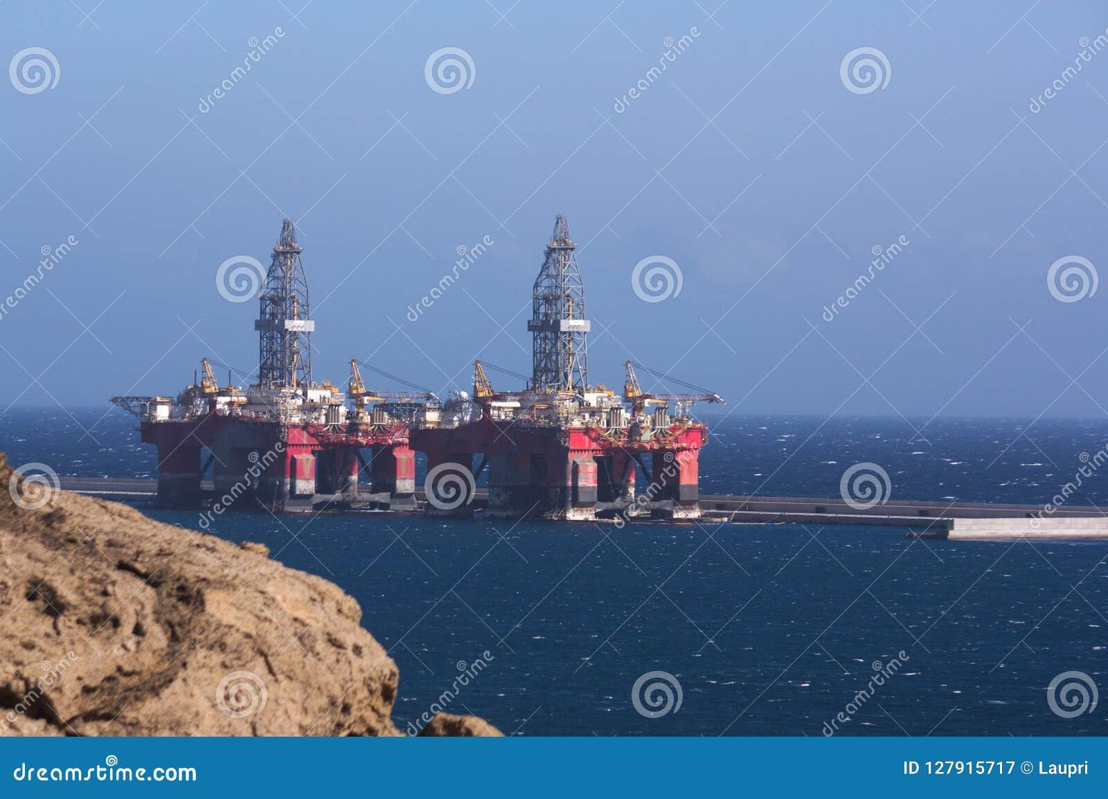 Duas plataformas petrolíferas amarradas a uma doca em um porto industrial
