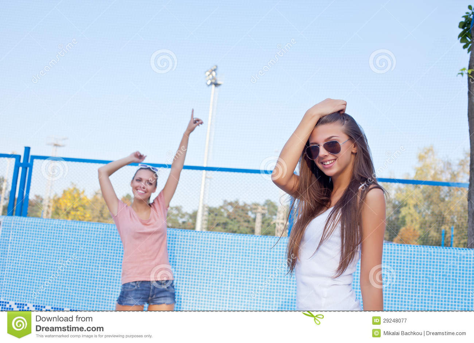 Duas raparigas bonitas no assoalho de uma associação vazia