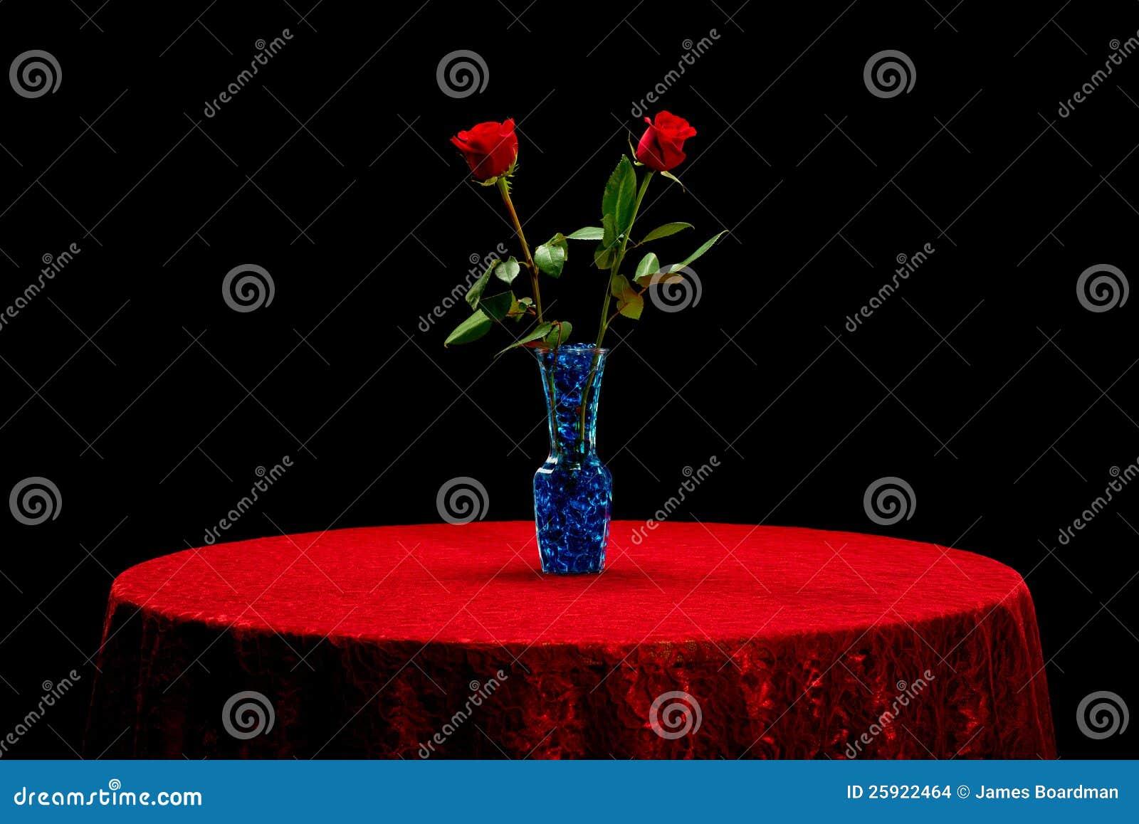 Duas rosas em um pano de tabela vermelho do laço