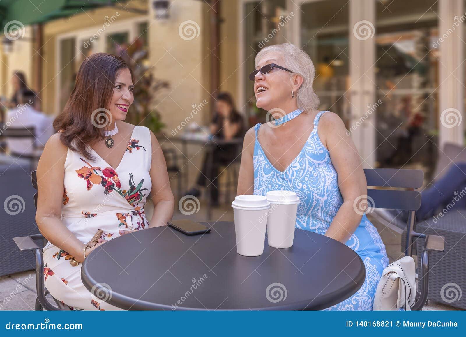 Duas senhoras maduras apreciam uma xícara de café no café exterior
