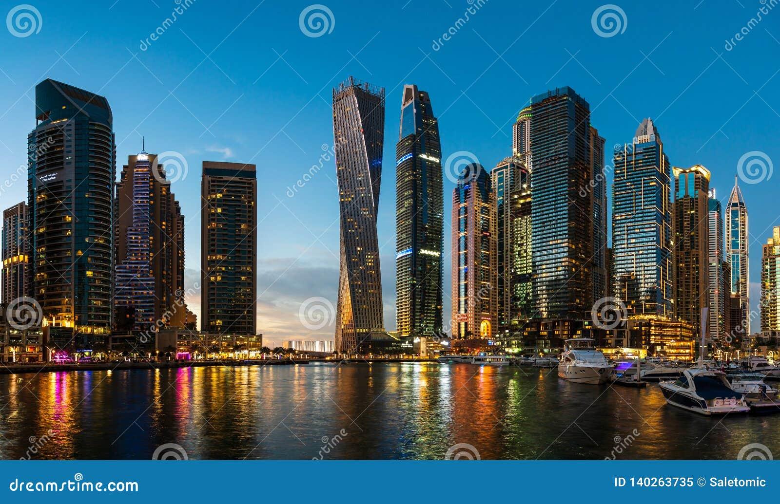 Dubai, Emiratos Árabes Unidos - 14 de fevereiro de 2019: Arranha-céus modernos do porto de Dubai e iate luxuosos na hora azul
