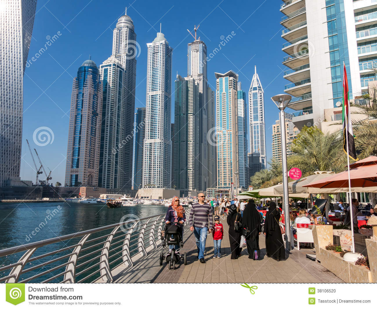 People walking on the Dubai Marina Walk with highrise buildings in the ...