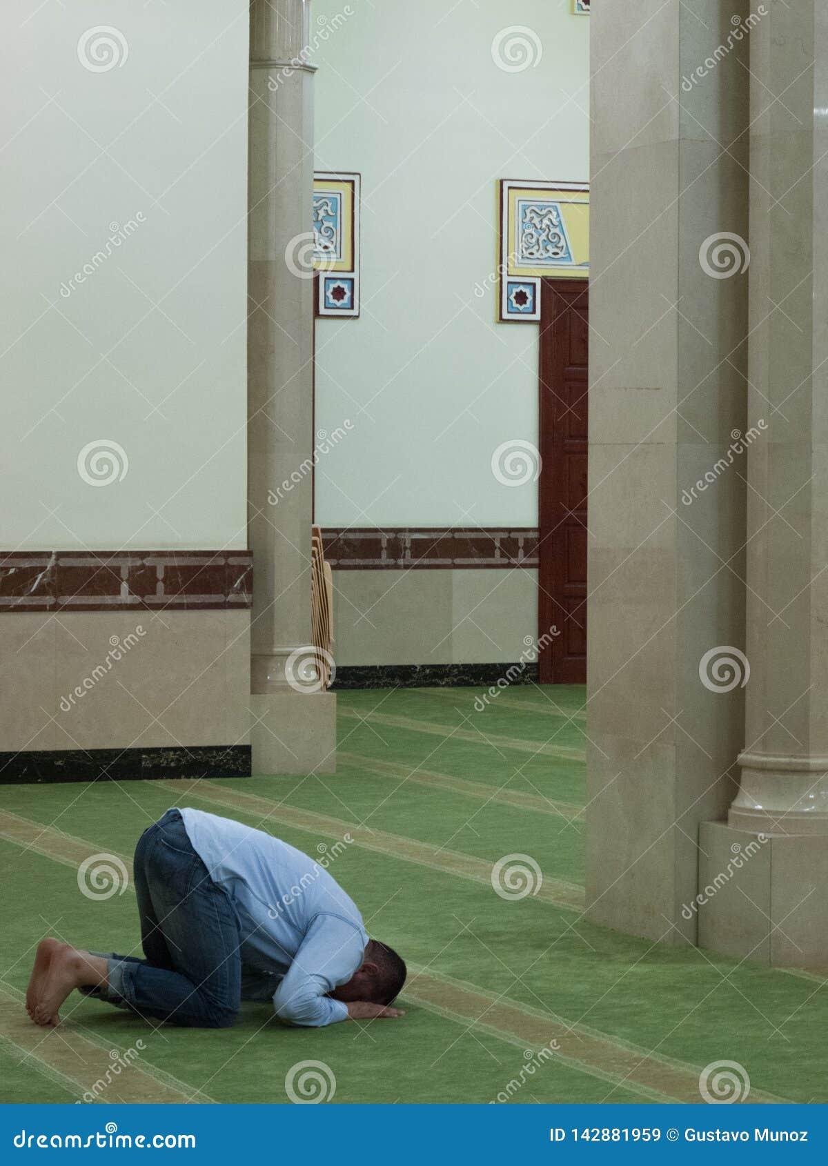 Dubai, UAE - março, 03, 2017: Um homem que reza em uma mesquita em Dubai