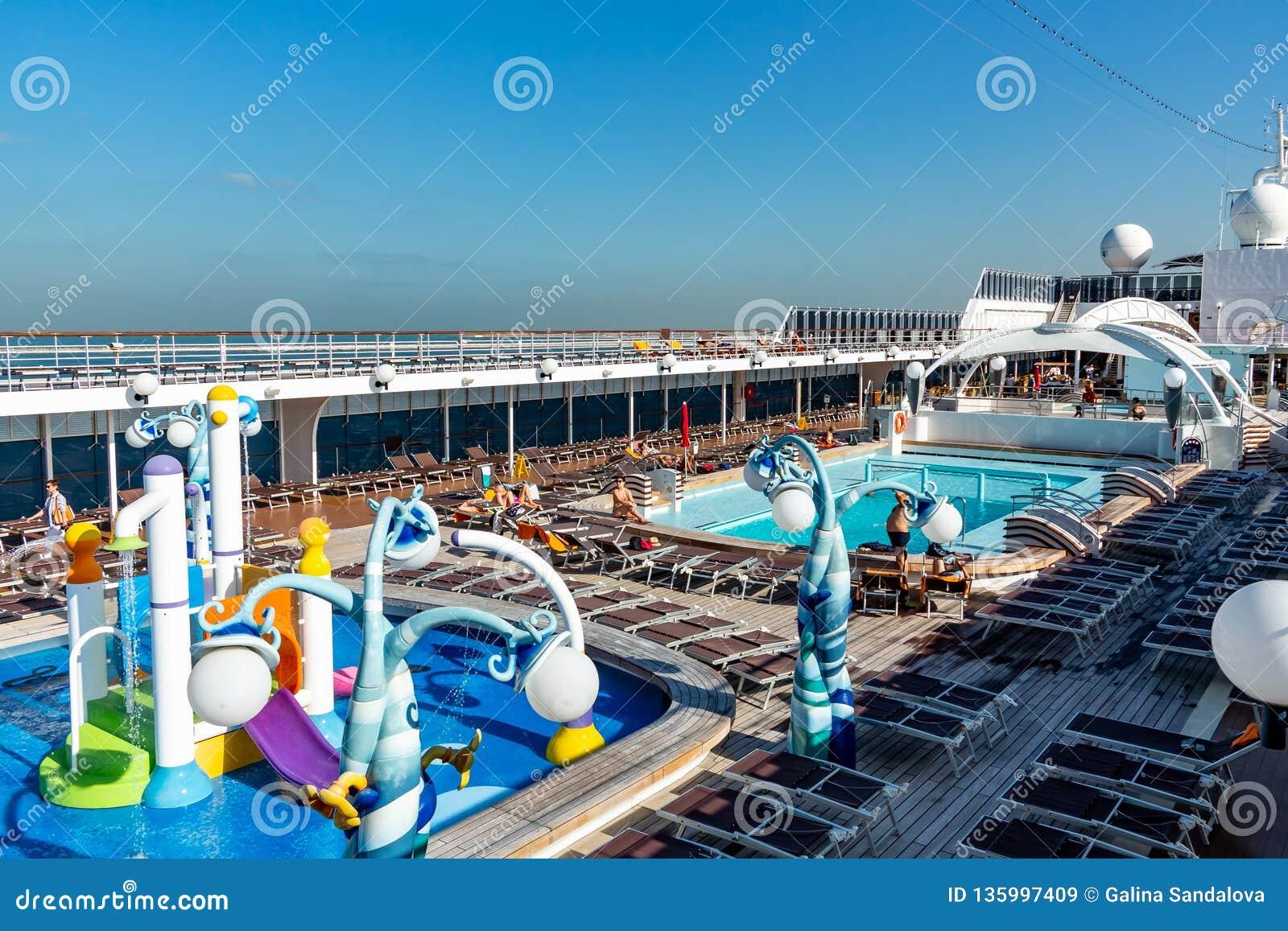 Dubai, United Arab Emirates - 12 de diciembre de 2018: cubierta superior del barco de cruceros con la piscina y los pasajeros de