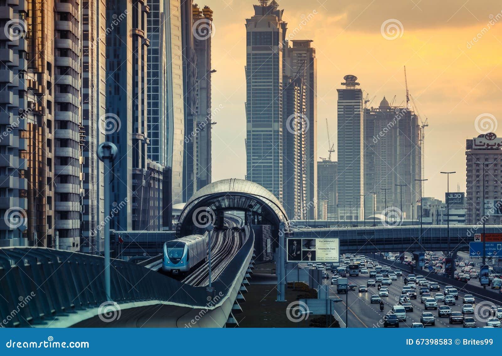 DUBAJ, UAE - GRUDZIEŃ 16, 2015: Dubaj ` s w centrum architektura w wieczór z metro jednoszynowym pociągiem przyjeżdża przy stacją