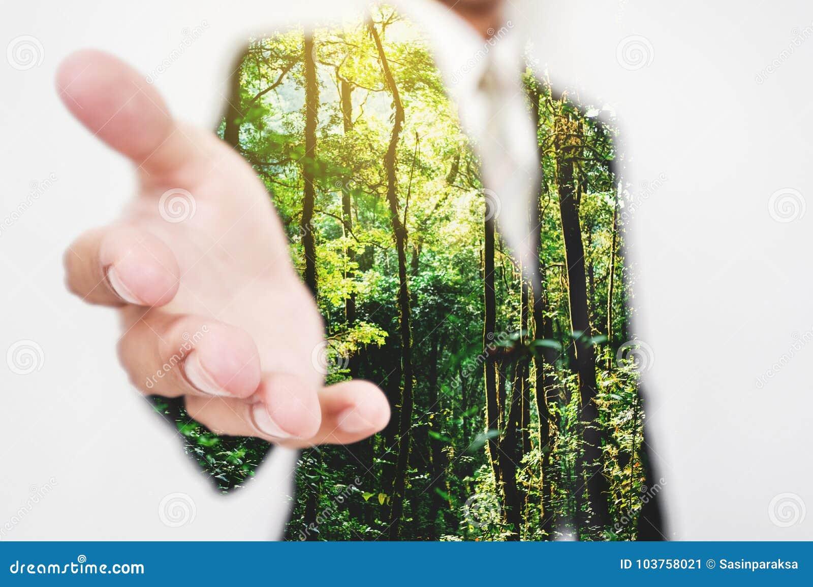 Dubbel exponering, affärsman som sträcker handen till handskakan med gröna träd i den skogEco vänskapsmatchen och den hållbara af