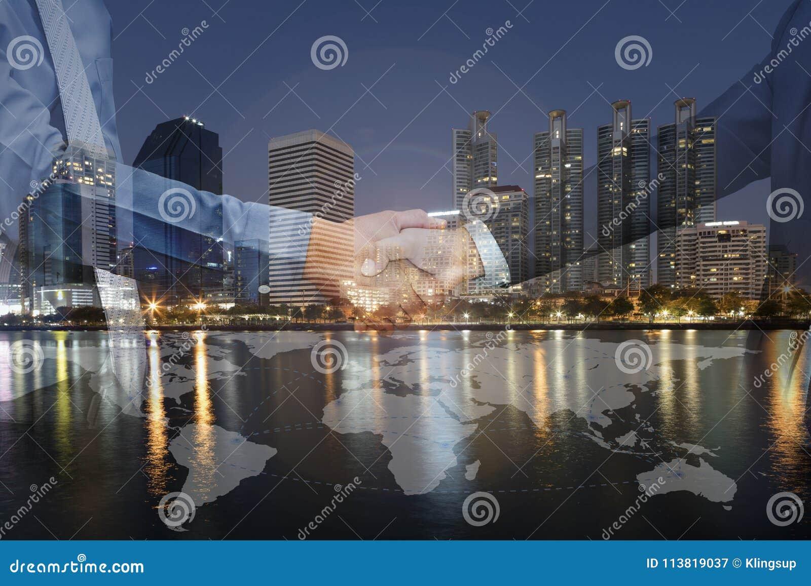 Dubbel exponering av affärsmanhandskakningen på cityscapenatt med