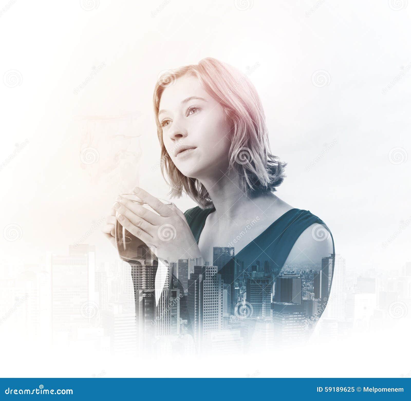 Dubbel exponering av den hållande tekoppen för ung kvinna med staden