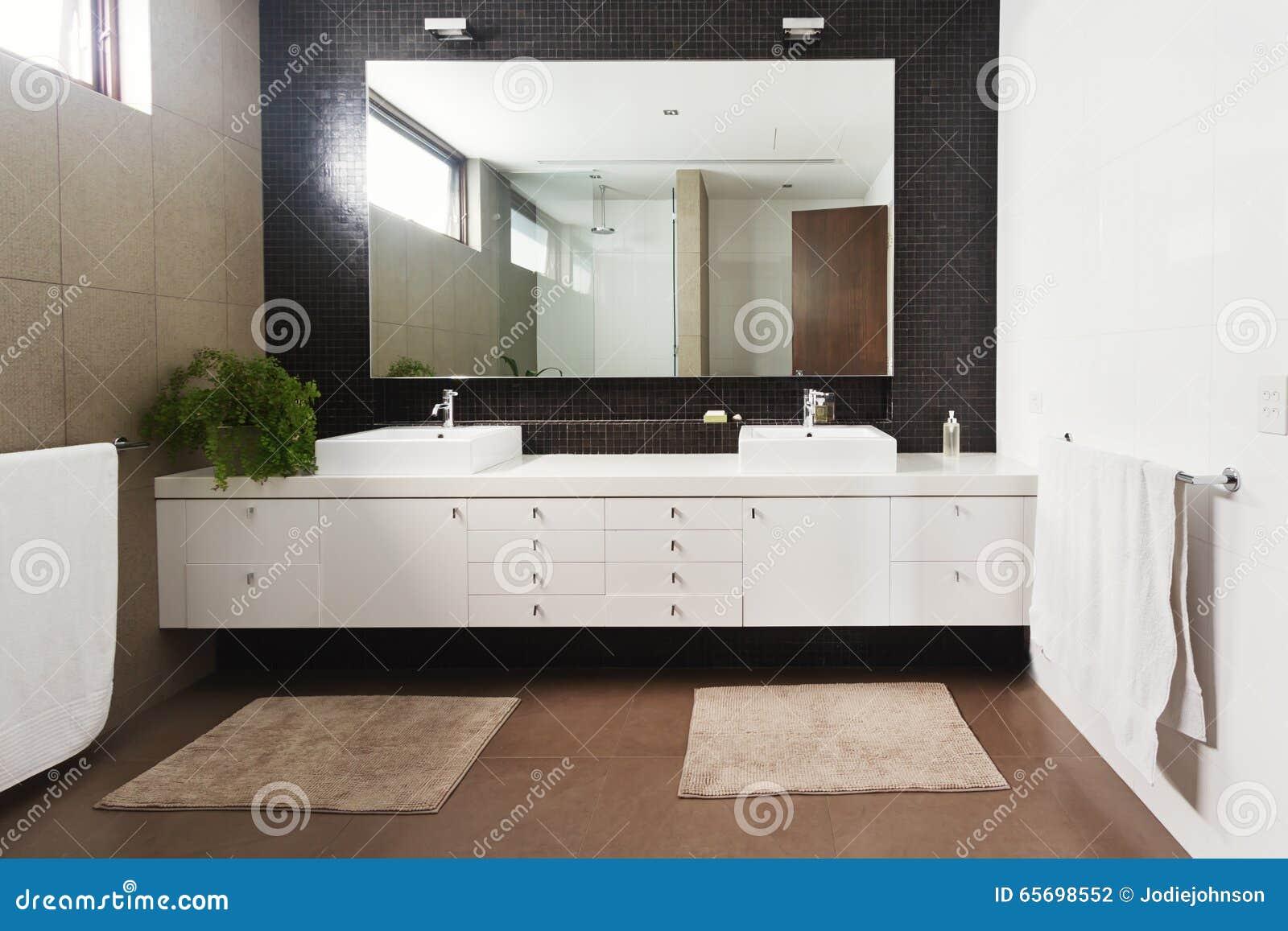 Dubbel handfatfåfänga och spegel i modernt nytt badrum arkivfoto ...