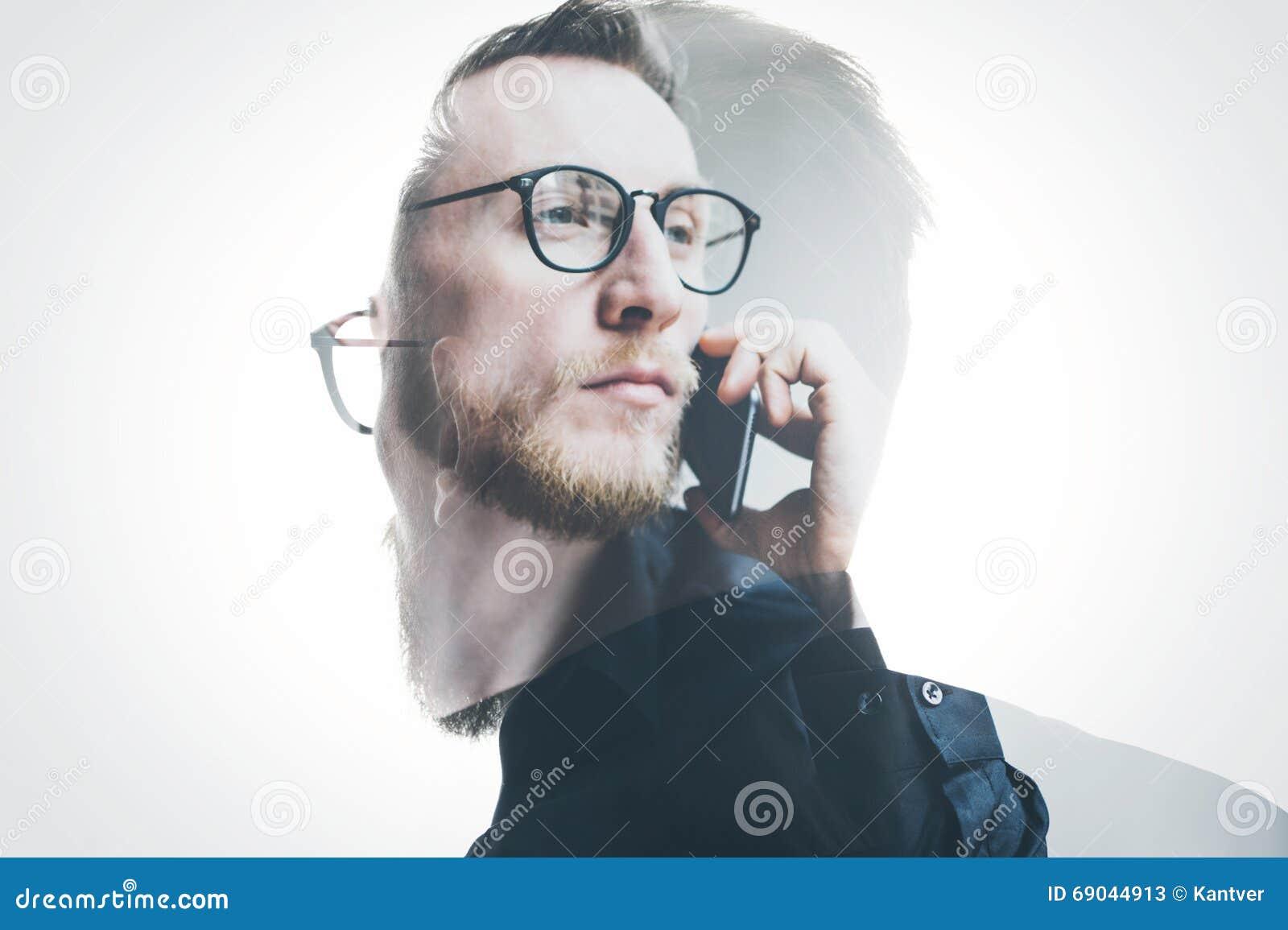 Dubbele blootstellings gebaarde bankier die zwarte overhemd en glazen draagt, die eigentijdse smartphonehand houden Geïsoleerd wi