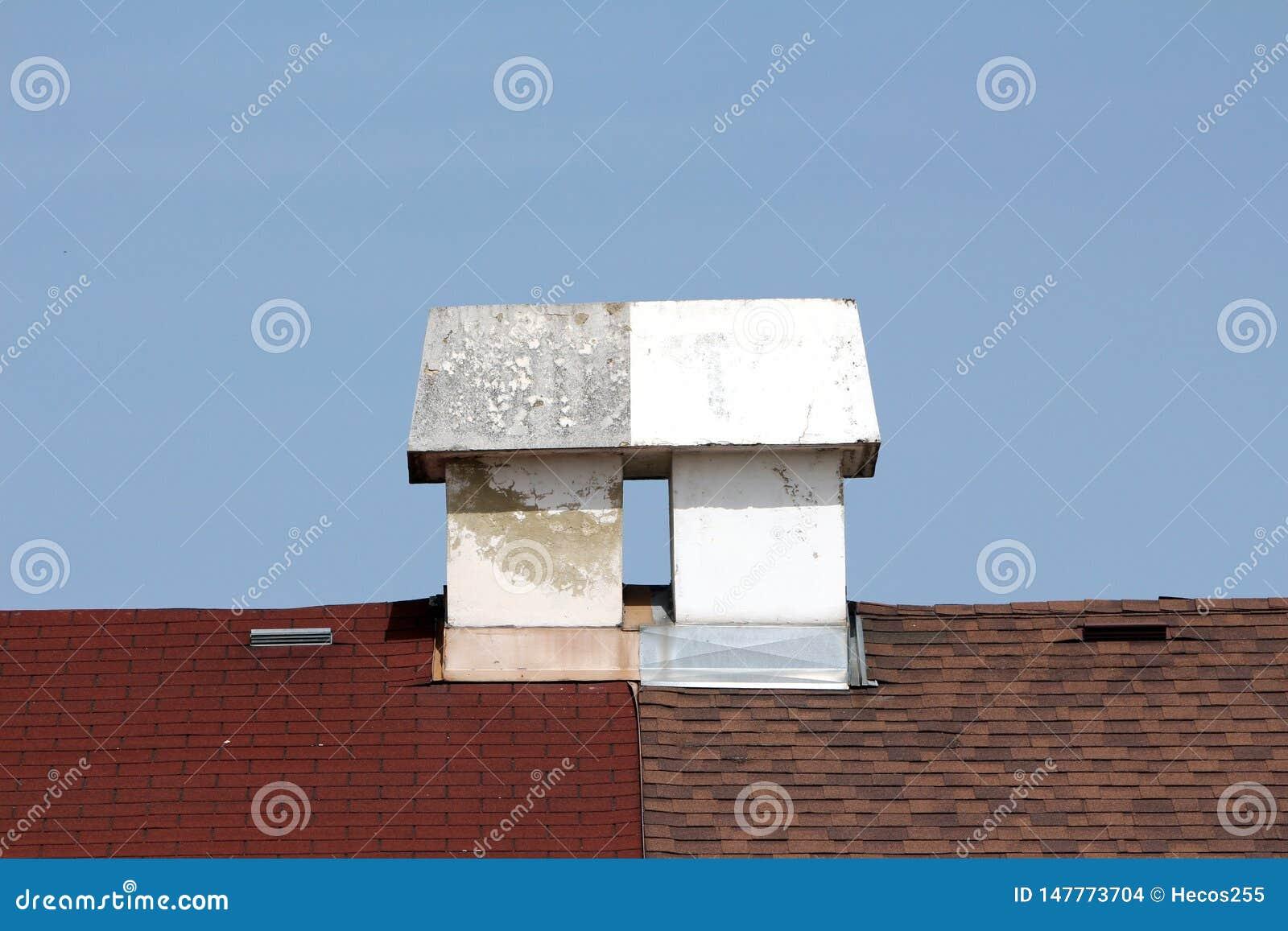Dubbele verbonden witte concrete schoorstenen bovenop huizendaken in bijlage op duidelijke blauwe hemelrug
