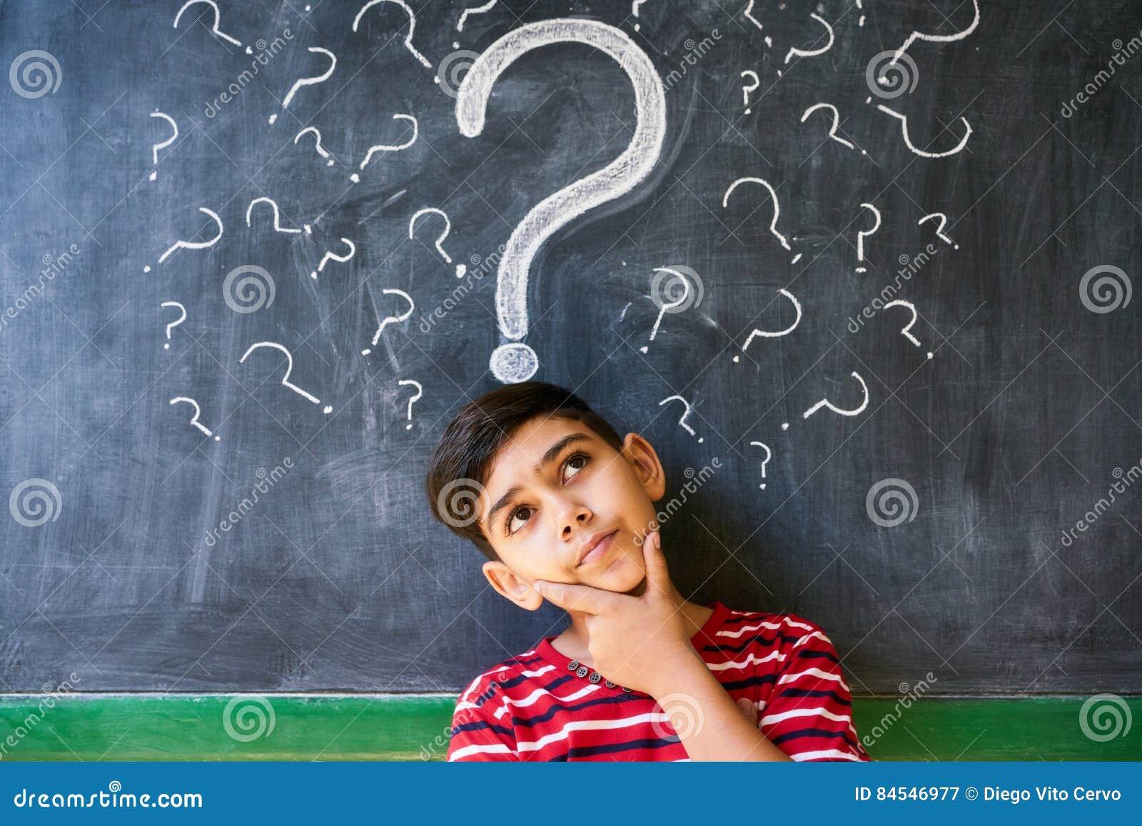 Dubbi e punti interrogativi con il bambino che pensa alla scuola