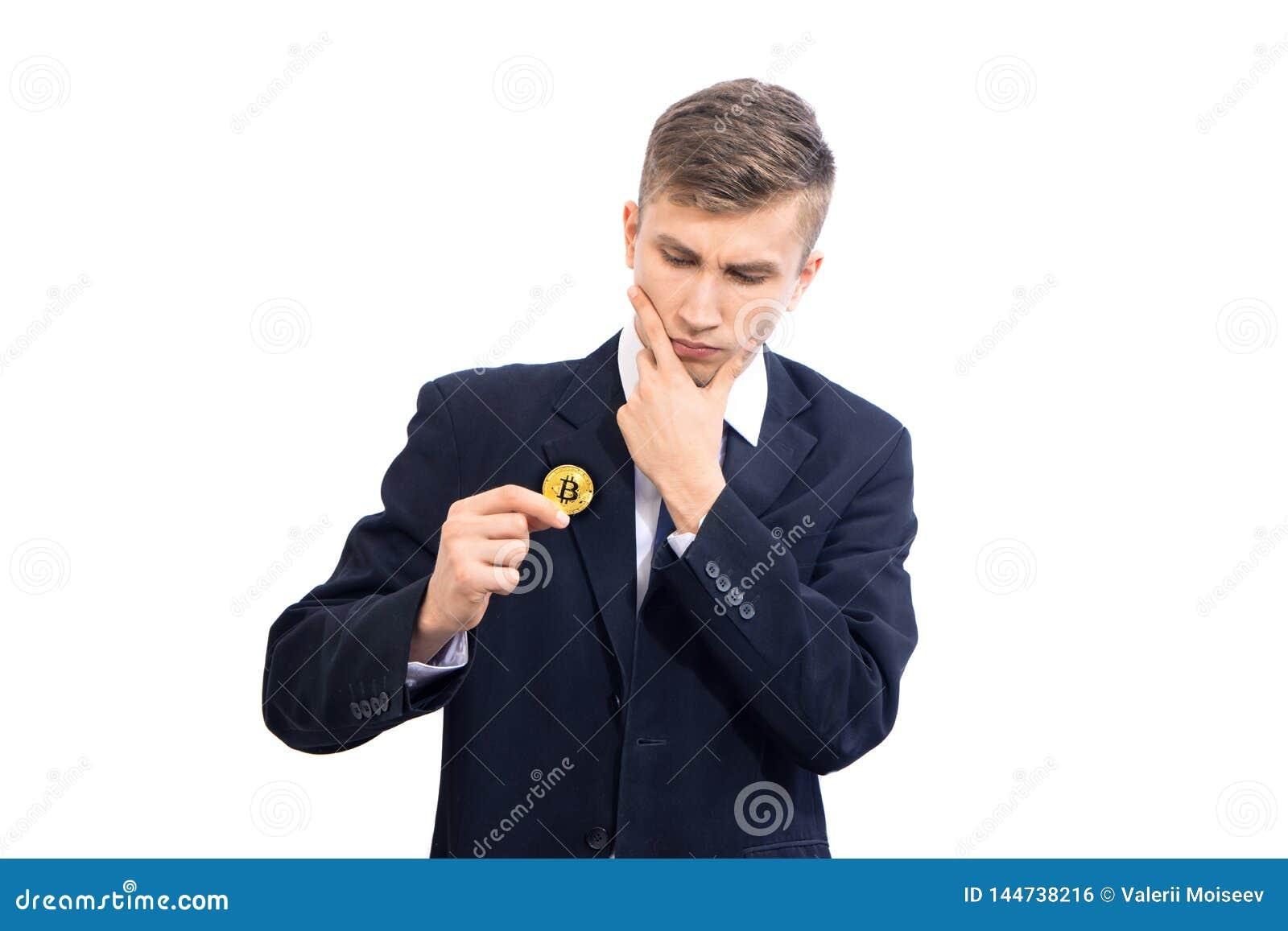 Dubbio del commerciante attraente giovane dell uomo d affari che tiene cryptocurrency del bitcoin, isolato su bianco
