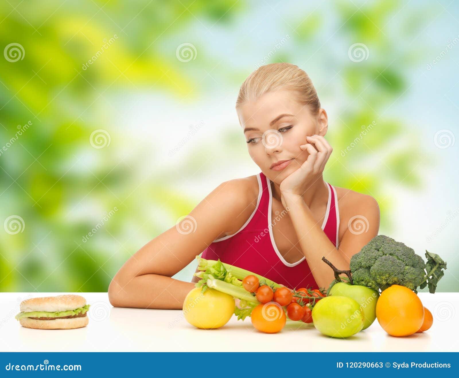 Dubbio della donna con i frutti che esaminano hamburger