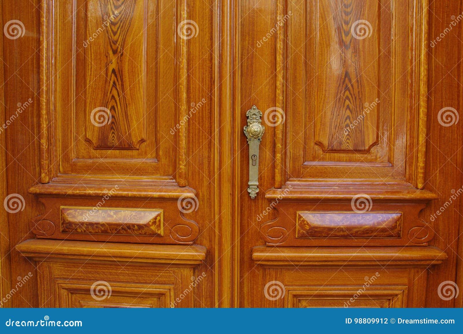 Dubbla dörrar för klassisk träingång med det guld- antika den dörrhandtaget och nyckelhålet