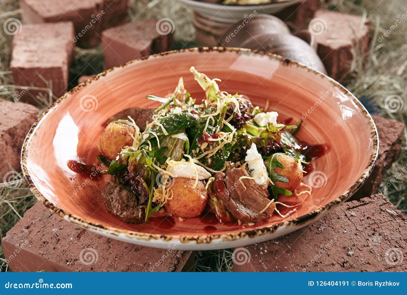 Duck Breast Salad con las bolas curruscantes de la patata en el heno rústico B del estilo