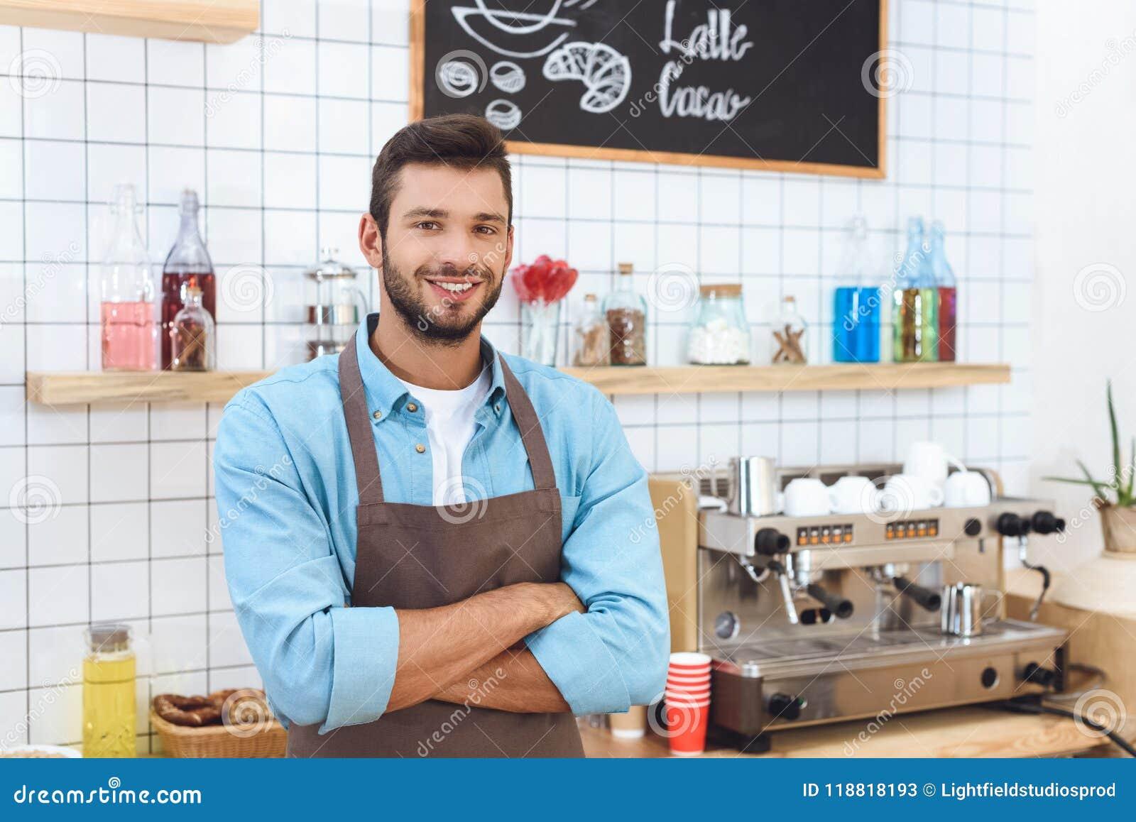 Dueño joven hermoso del café en el delantal que se coloca con los brazos cruzados y la sonrisa