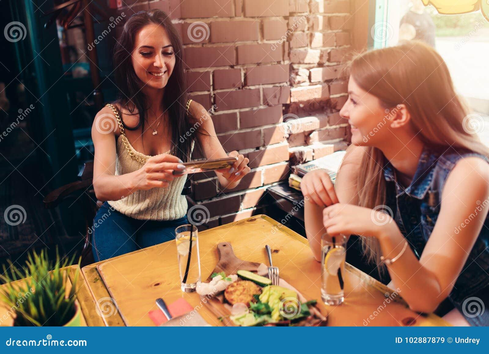Due amiche che hanno pranzo sano in caffè Giovane donna che prende immagine di alimento con l invio dello smartphone sui media so
