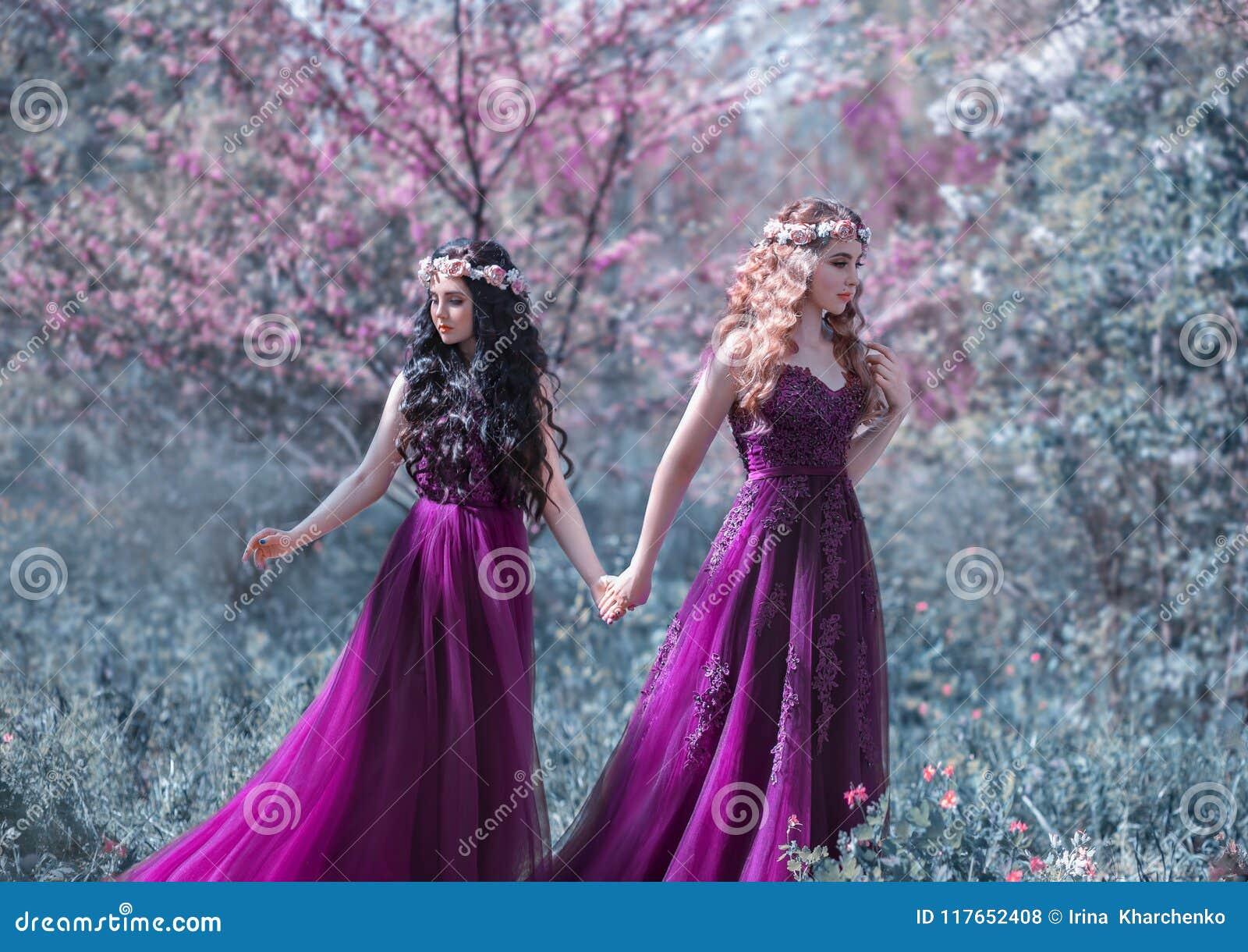 Due amiche, un biondo e un castana, stanno tenendo per mano Bello giardino di fioritura del fondo Le principesse sono vestite den