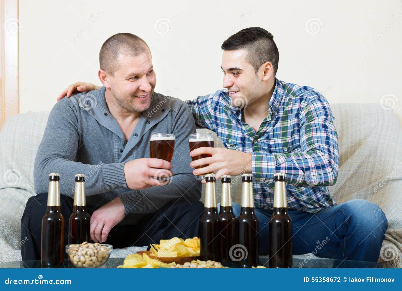 Due amici che bevono birra a casa
