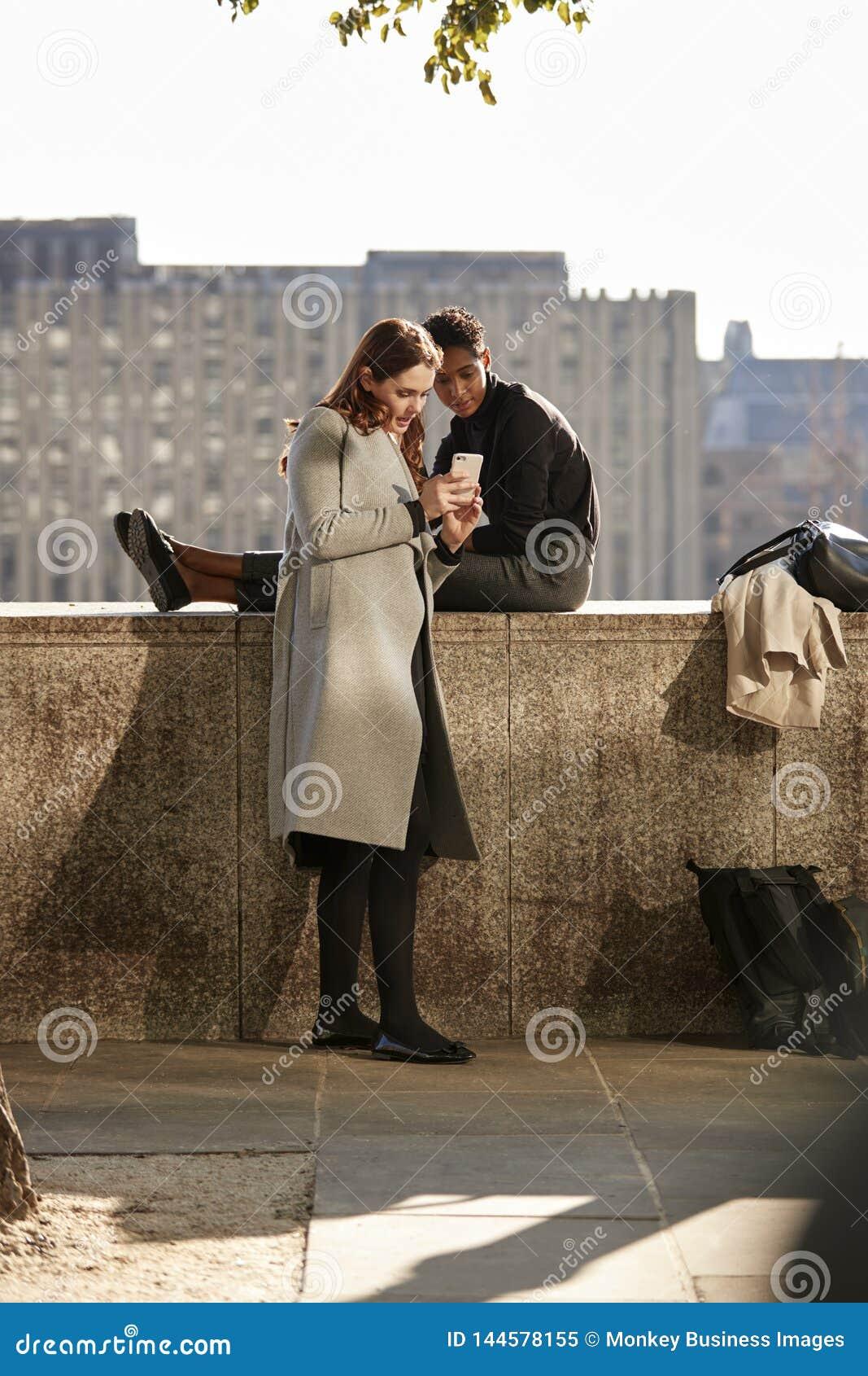 Due amici femminili che prendono una rottura sull argine dal Tamigi, esaminante uno smartphone, retroilluminato