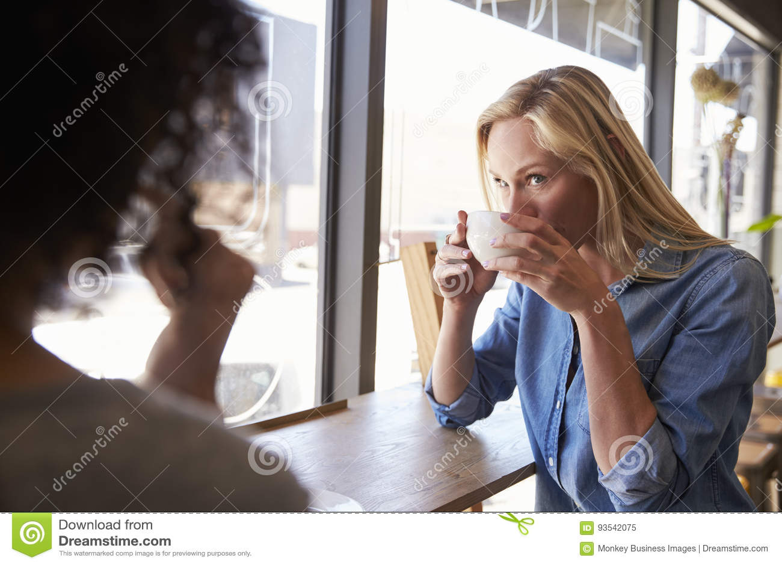 Due amici femminili che si incontrano nella caffetteria