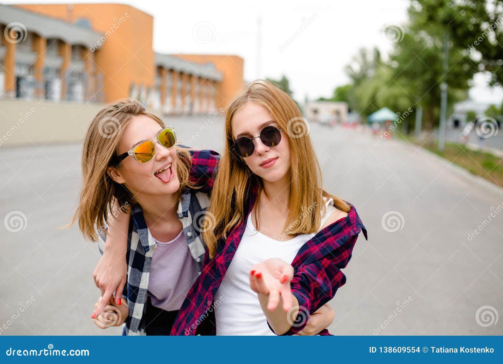 Due amici femminili sorridenti che si abbracciano sulla via Concetto di feste, di vacanza, di amore e di amicizia