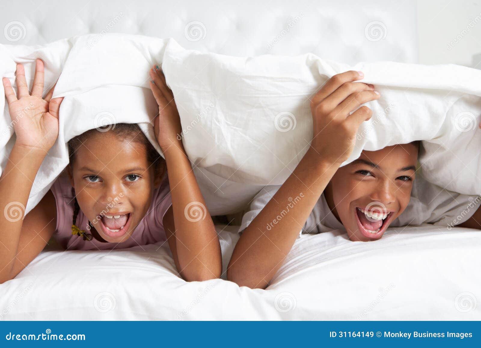 Due bambini che si nascondono sotto il piumino a letto immagine stock immagine di avendo - Letto che si chiude ...