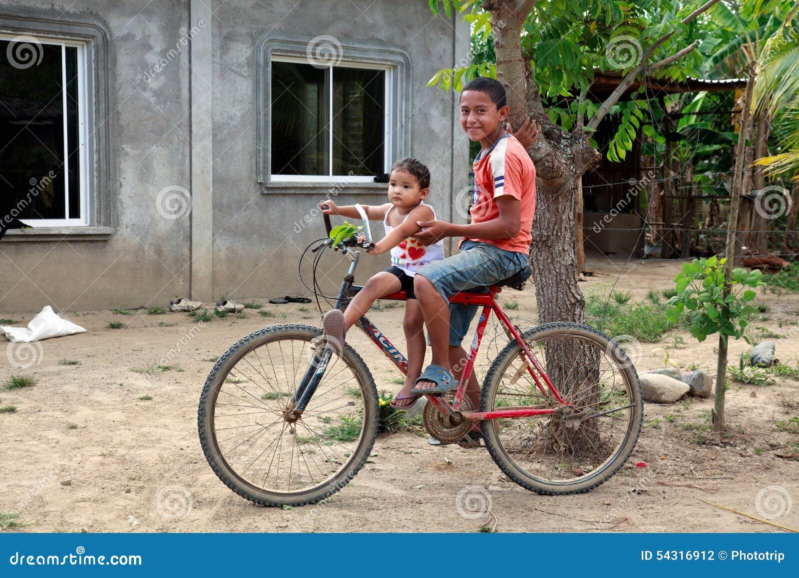 Due Bambini Del Honduran Che Si Siedono Sulla Bicicletta In