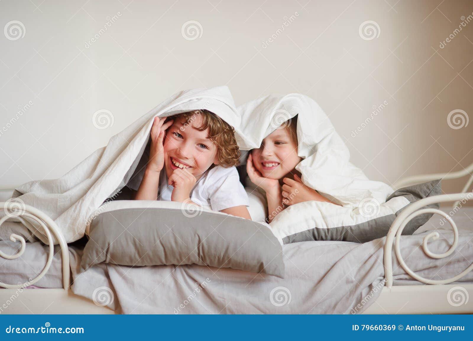 Due bambini fratello e sorella squirmy sul letto nella - Camera da letto bambini ...