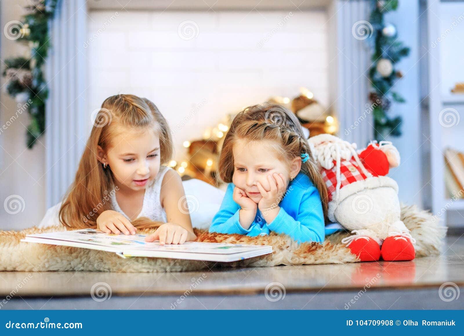 Due bambini hanno letto un libro Due sorelle Nuovo anno di concetto, Chris allegro
