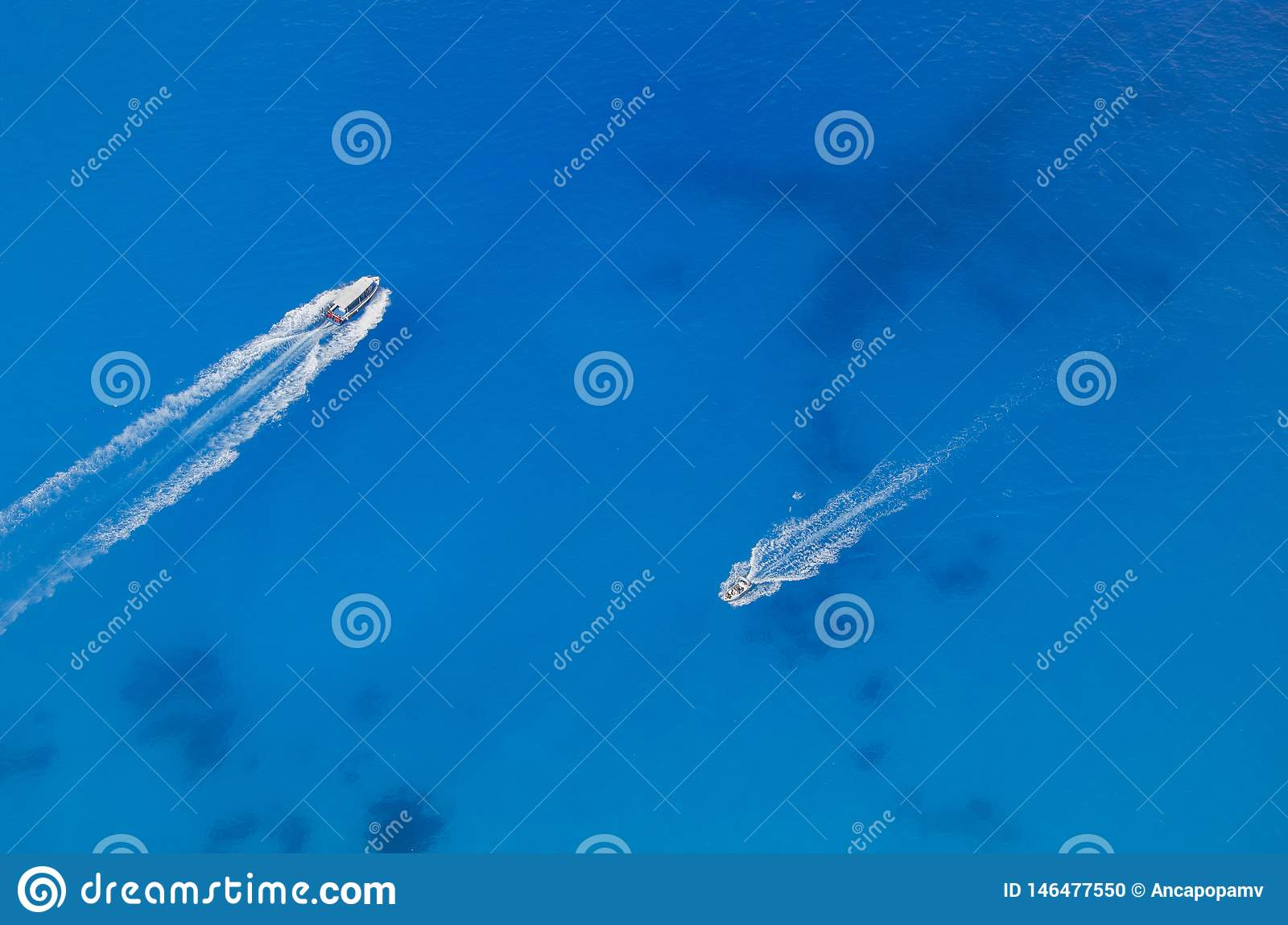 Due barche opposte su chiara acqua blu
