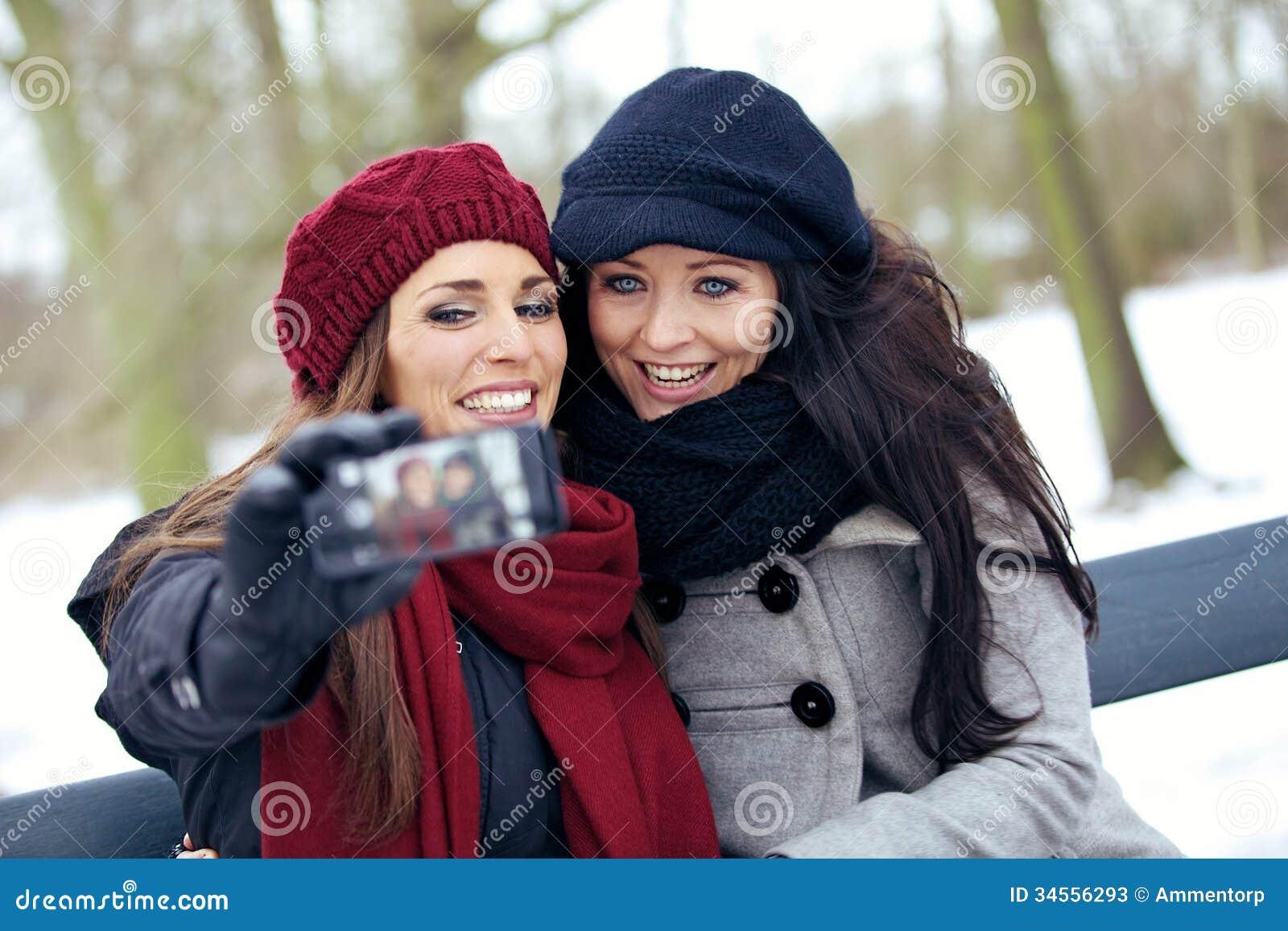 Due belle donne con il telefono della macchina fotografica in un parco