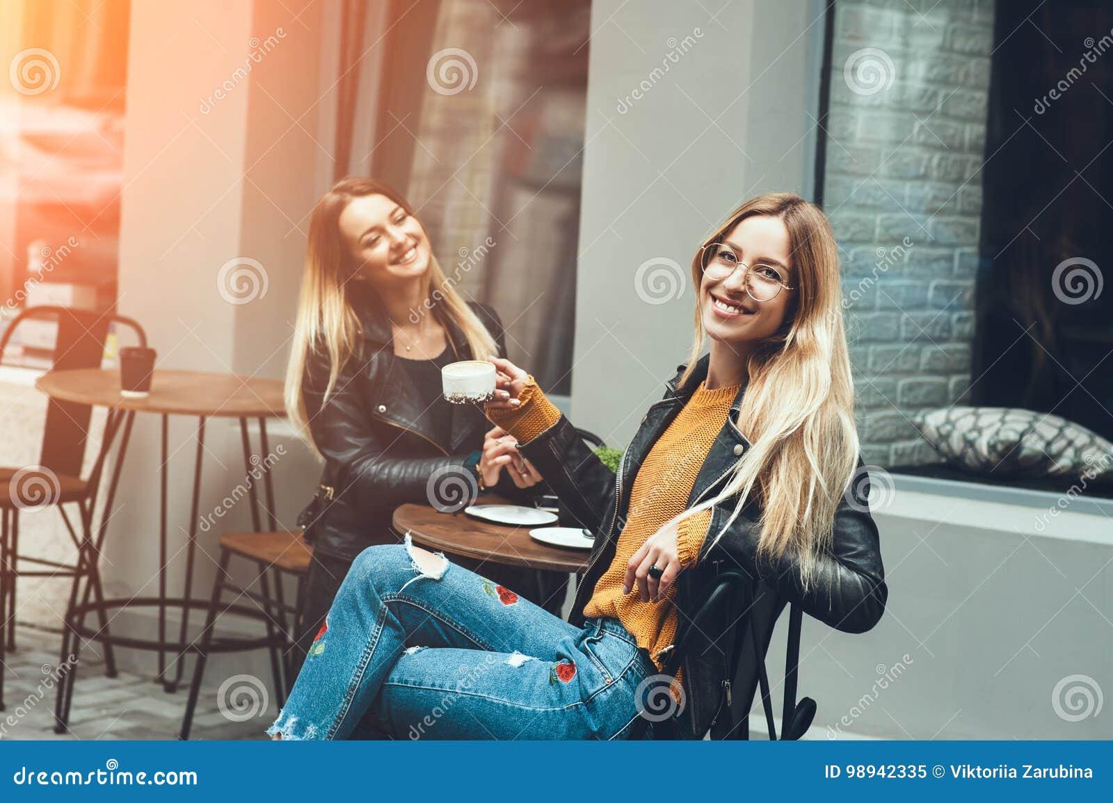 Due belle giovani donne in vestiti di modo che hanno resto che parlano e caffè bevente in ristorante all aperto
