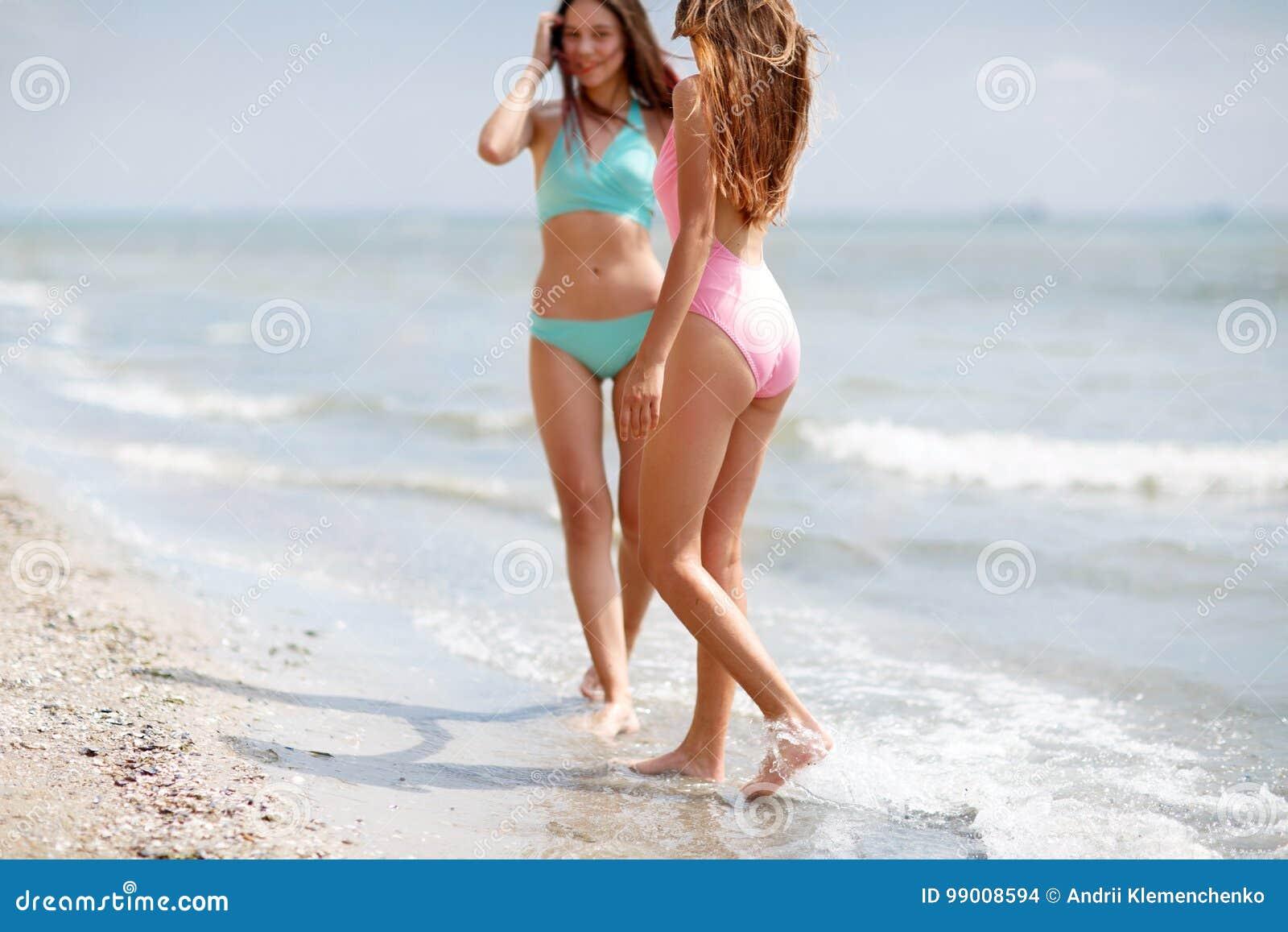 Due belle ragazze in costumi da bagno variopinti su un fondo del mare signore che camminano - Donne in bagno in due ...