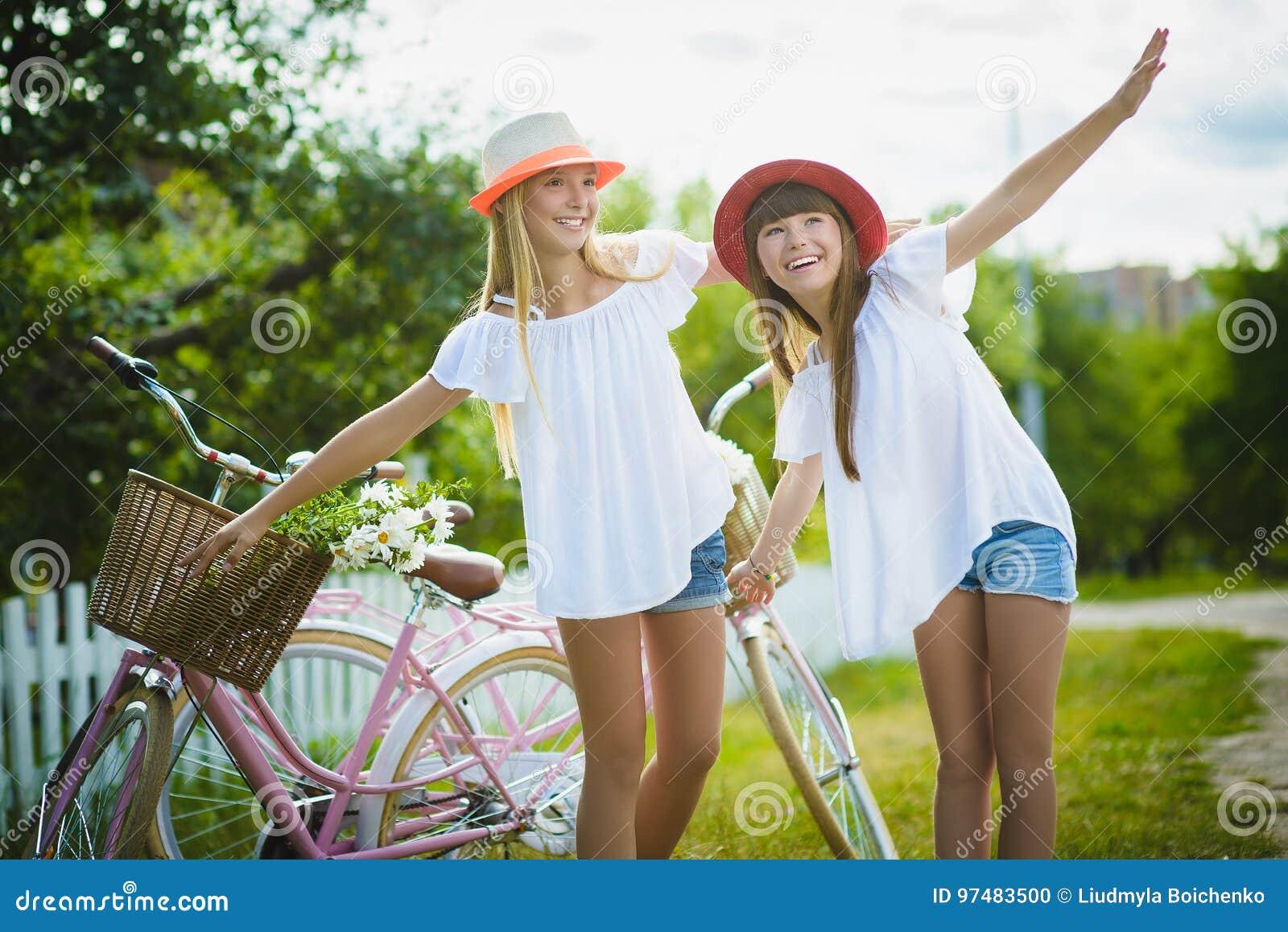 Due belle ragazze felici dei pantaloni a vita bassa che ridono e che posano per la macchina fotografica con le bici
