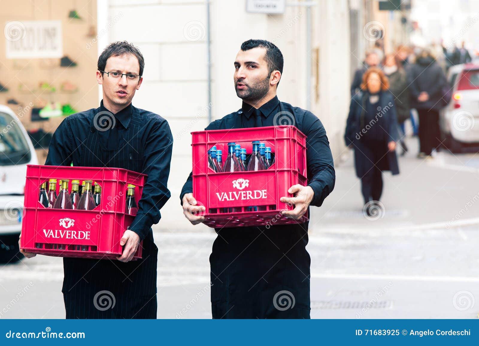 Due Camerieri Che Portano Le Casse Di Vino Nel Centro Storico Di ...