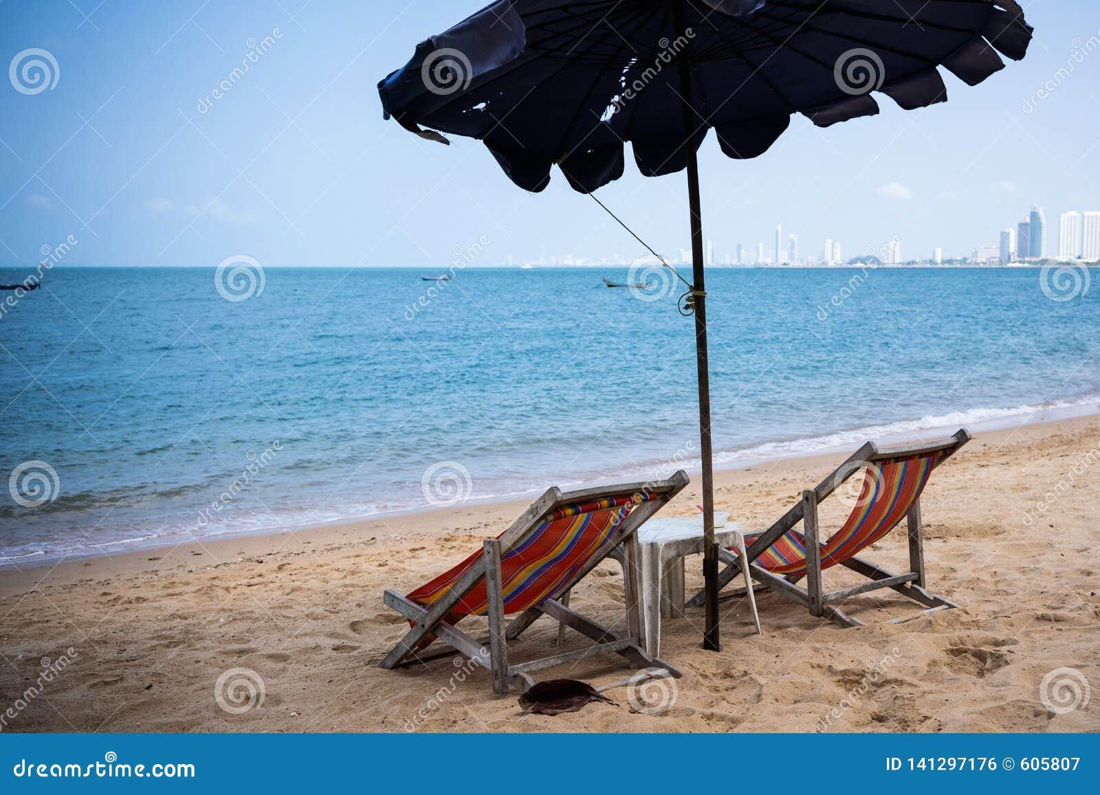 Due chaise-lounge e un ombrello sul mare blu sulla spiaggia di Pattaya, Tailandia Vista posteriore