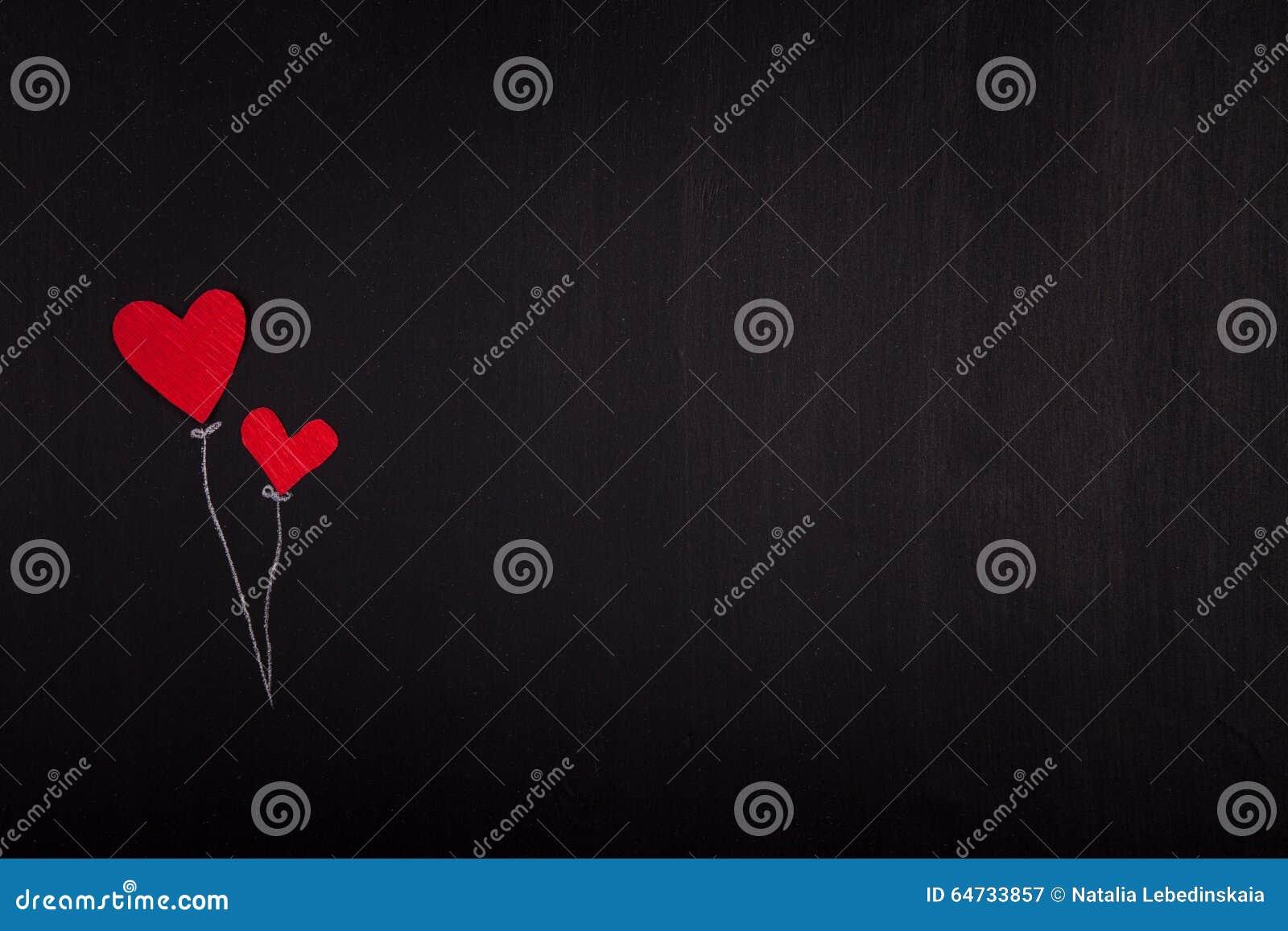 Due cuori di carta rossi su un San Valentino della lavagna