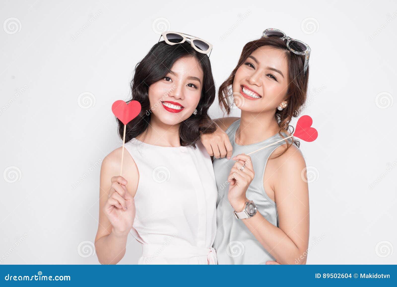 Due donne alla moda in vestiti piacevoli che stanno insieme e nella tenuta