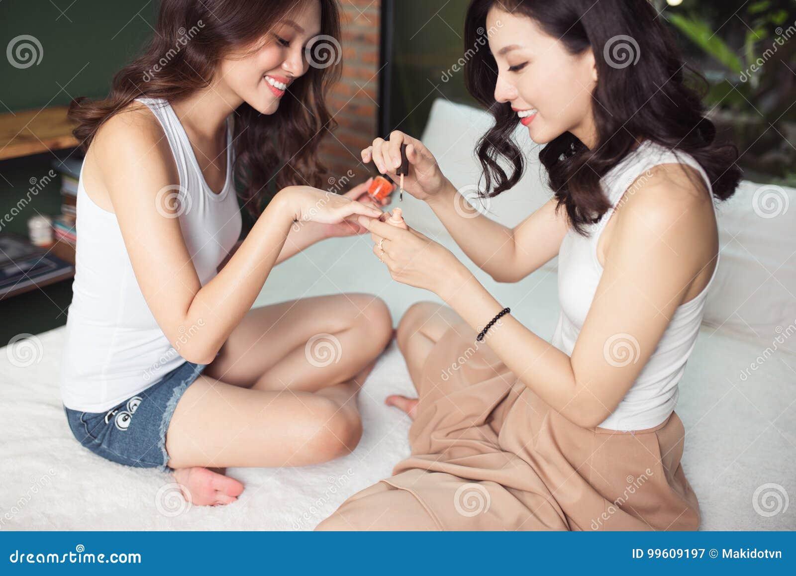 Due Donne Asiatiche Nella Camera Da Letto Sul Letto ...