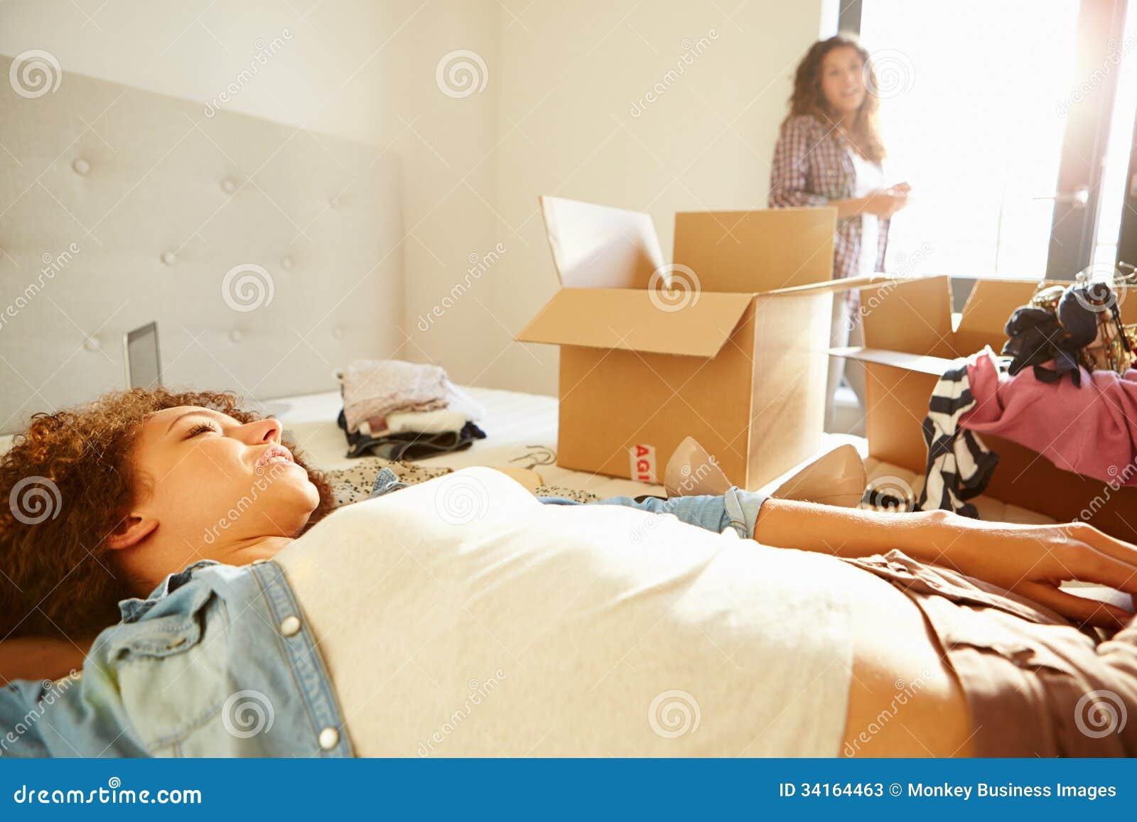 due donne con le scatole in camera da letto che entra nella nuova ... - Donne In Camera Da Letto