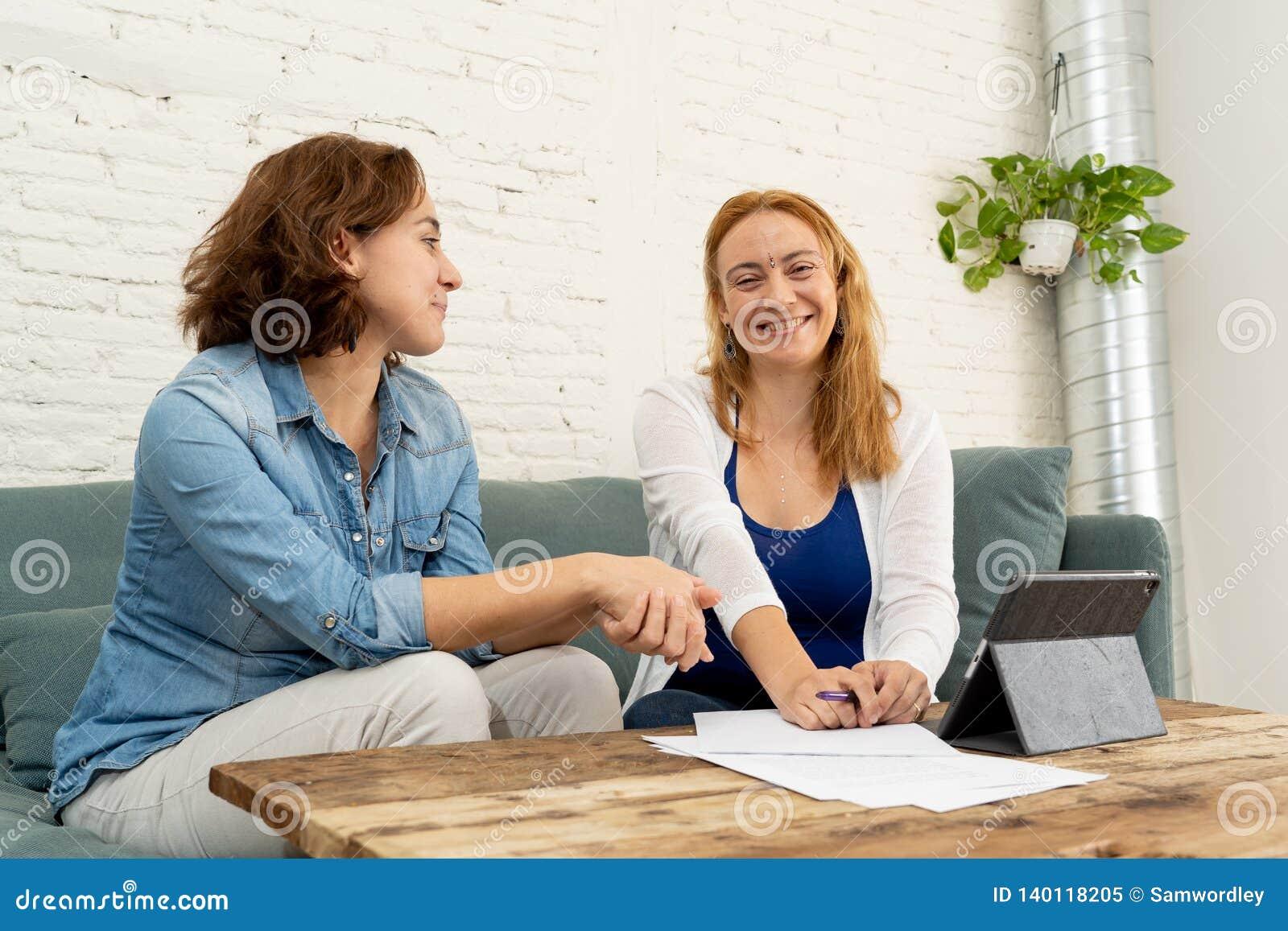 Due donne degli imprenditori che lavorano insieme sulla progettazione sulla compressa per il loro affare online