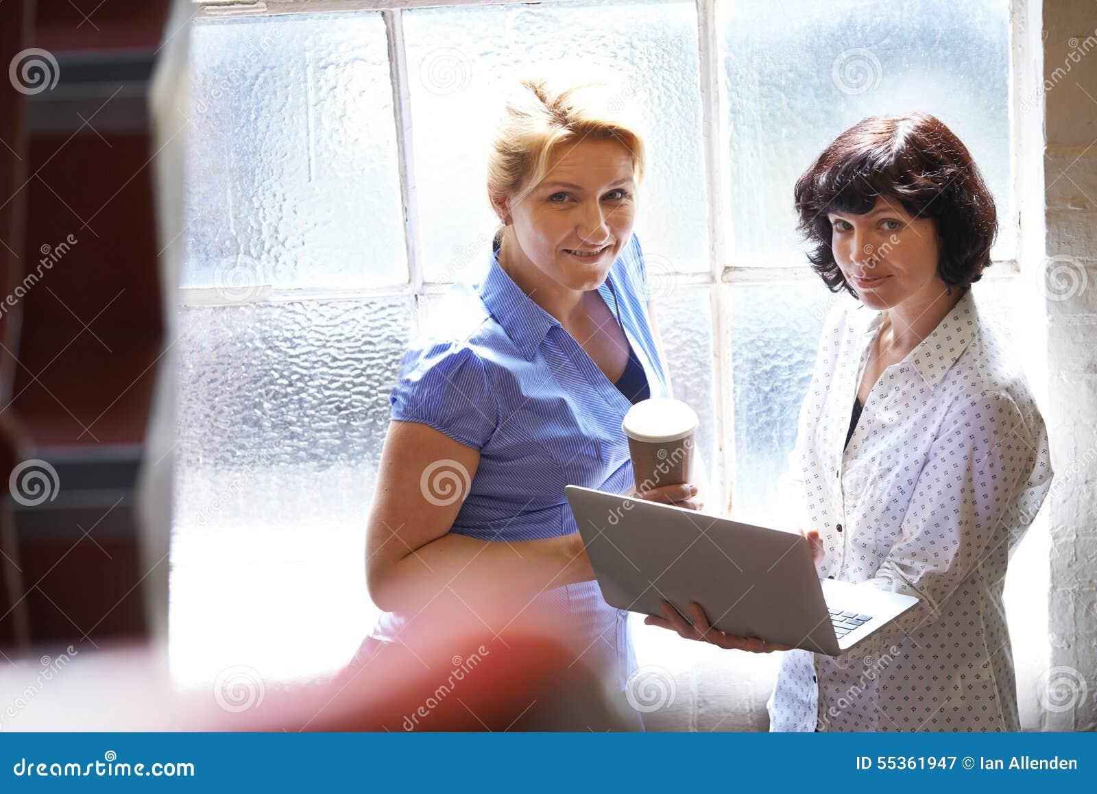 Due donne di affari che hanno riunione informale in ufficio