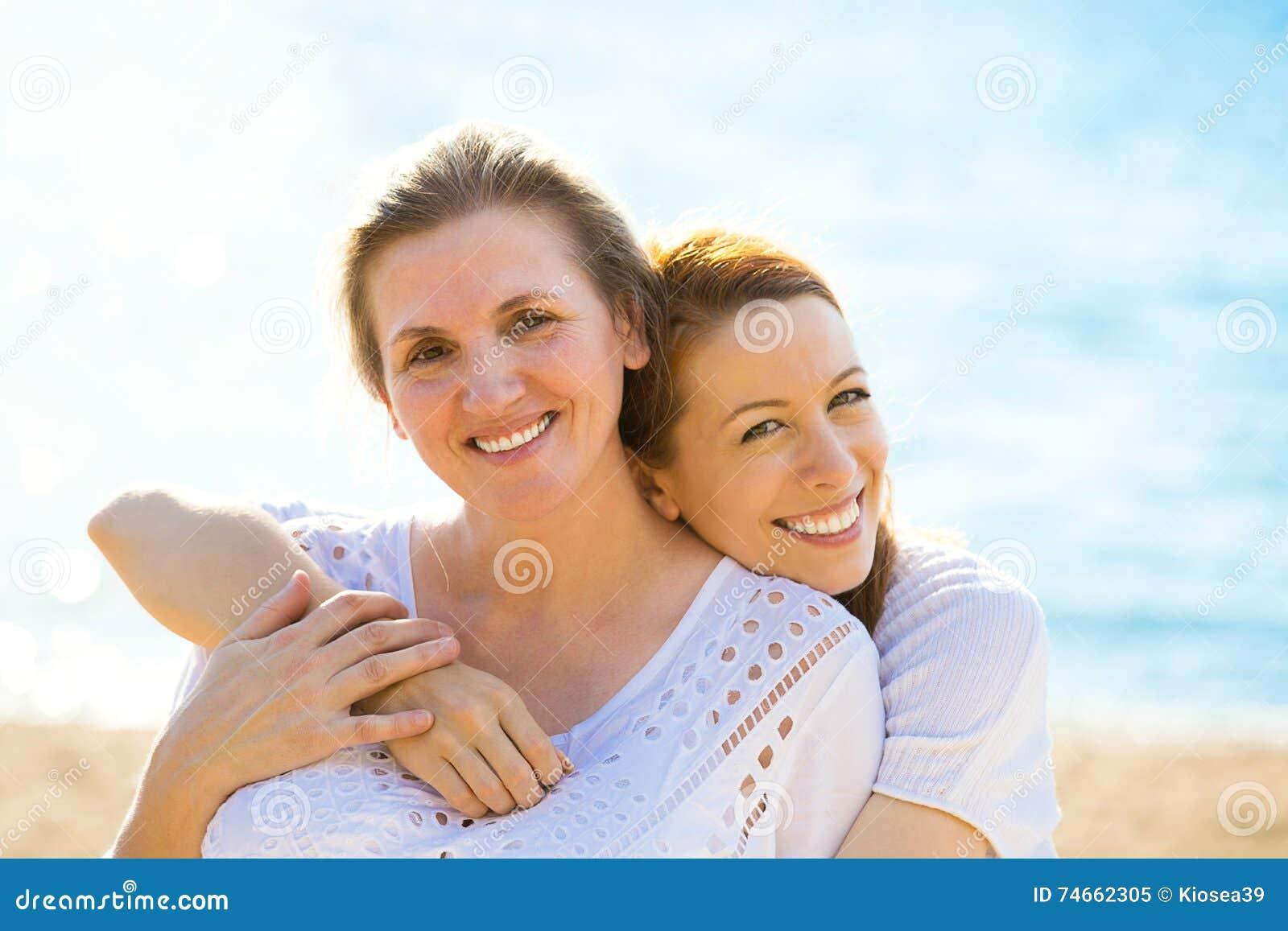 Due donne madre e figlia dell adulto che gode della vacanza sulla spiaggia