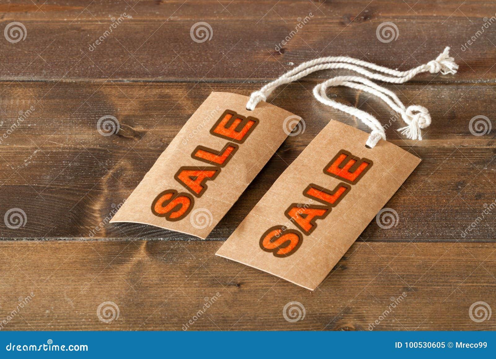 Due etichette di vendita su una tavola di legno