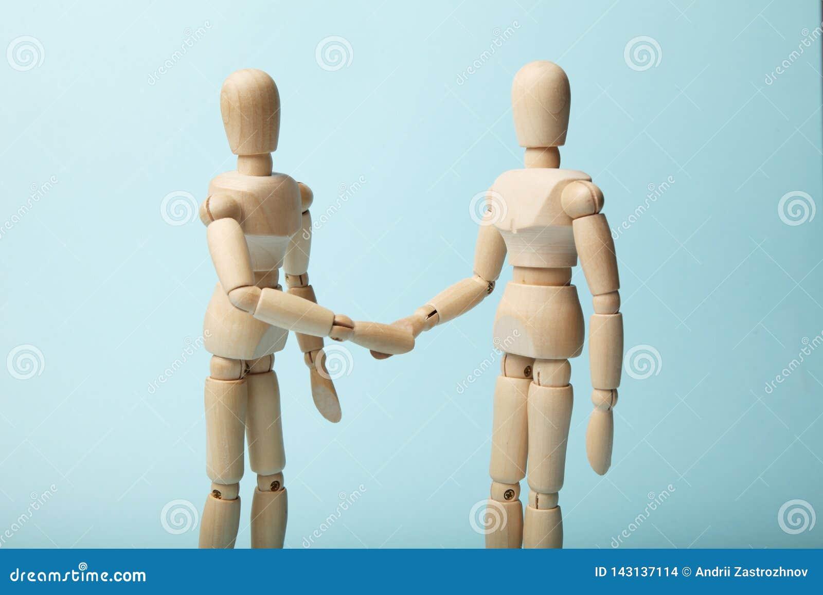 Due figure di legno delle mani di scossa dell uomo