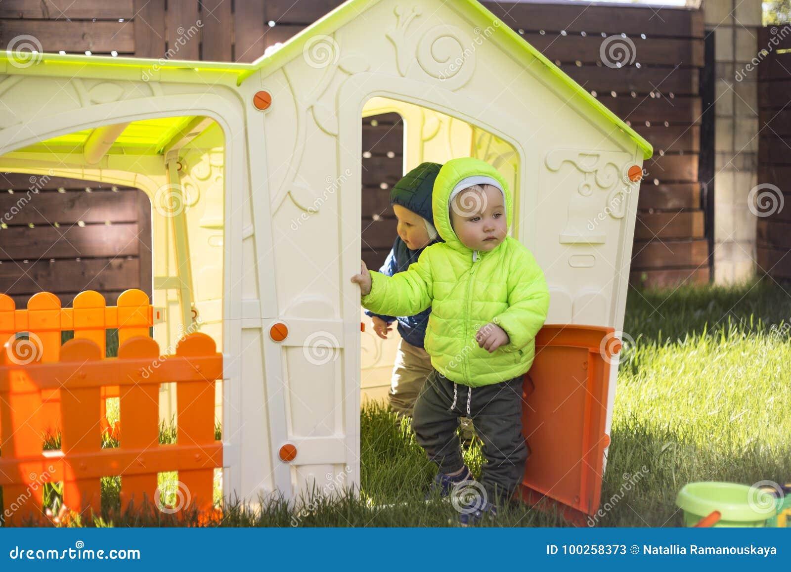 Due fratelli gemelli giocano e si divertono nella grande casa del giocattolo del campo da giuoco